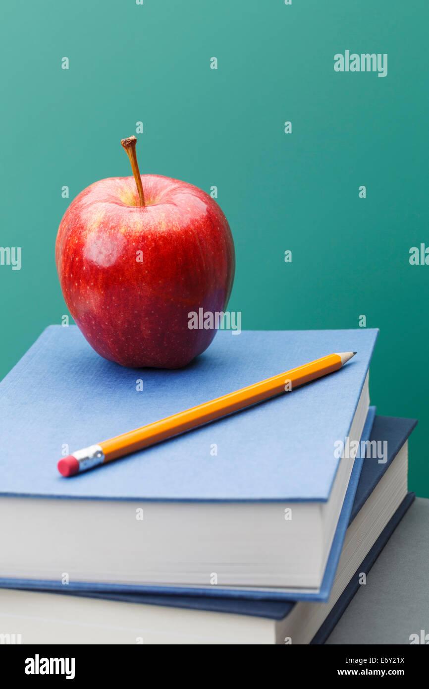 Grünen Tafel, Schulbücher, geschärft gelbe Bleistift und roter Apfel im Klassenzimmer mit Textfreiraum. Stockbild
