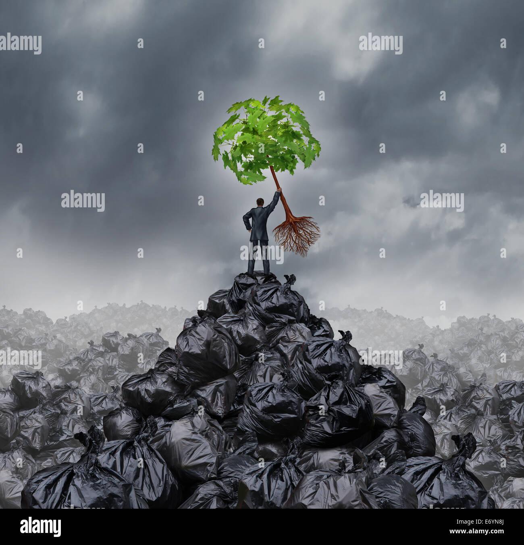 Grüne Geschäftsmann Konzept als ein Mann oben auf einem Berg Haufen Müll hält ein grünes Stockbild