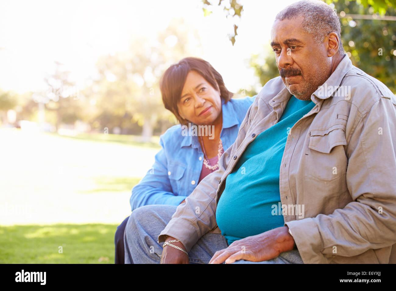 Ältere Frau trösten unglücklich Senior Mann im freien Stockbild