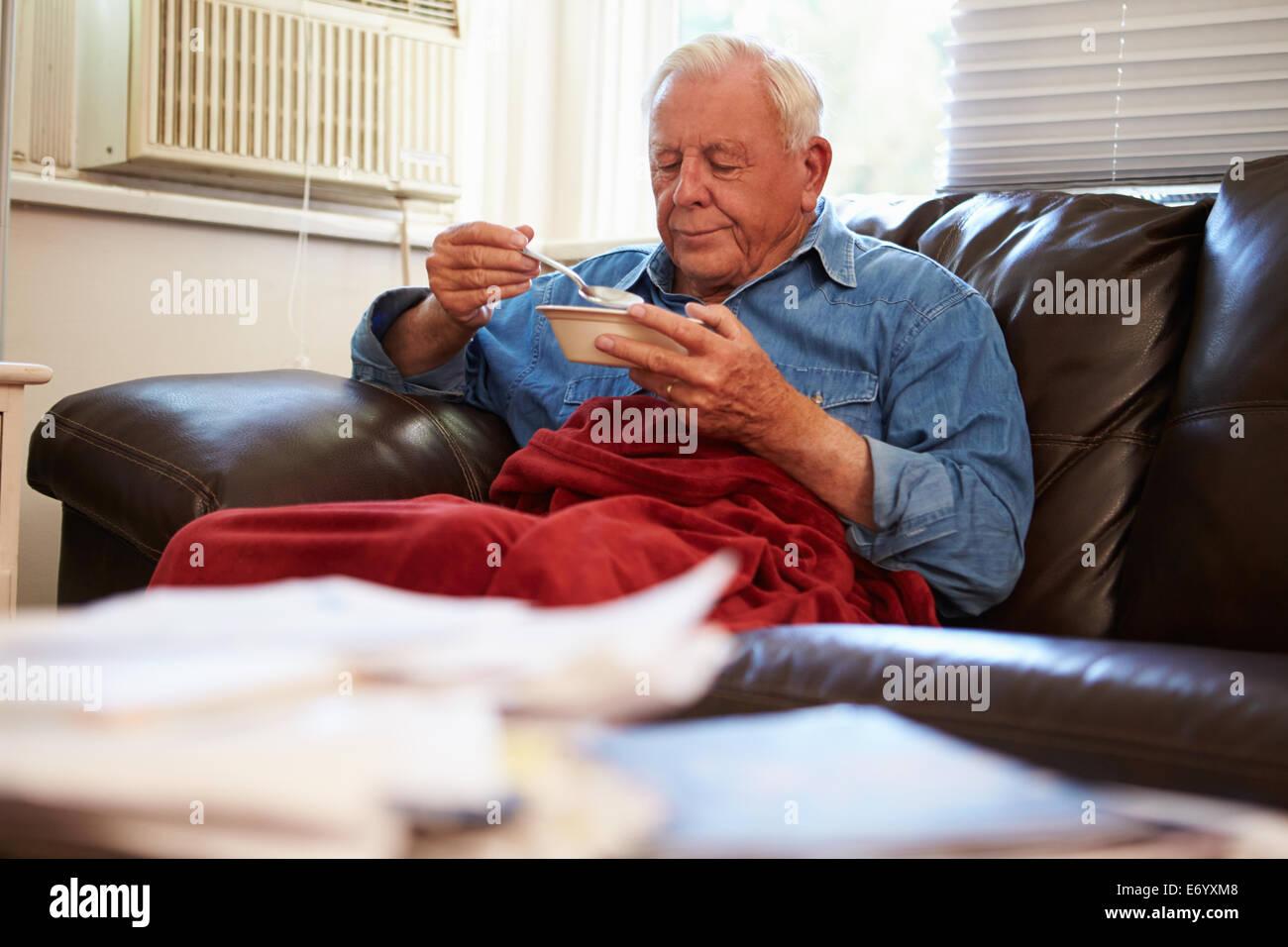 Ältere Mann mit schlechter Ernährung unter Decke Warm zu halten Stockbild