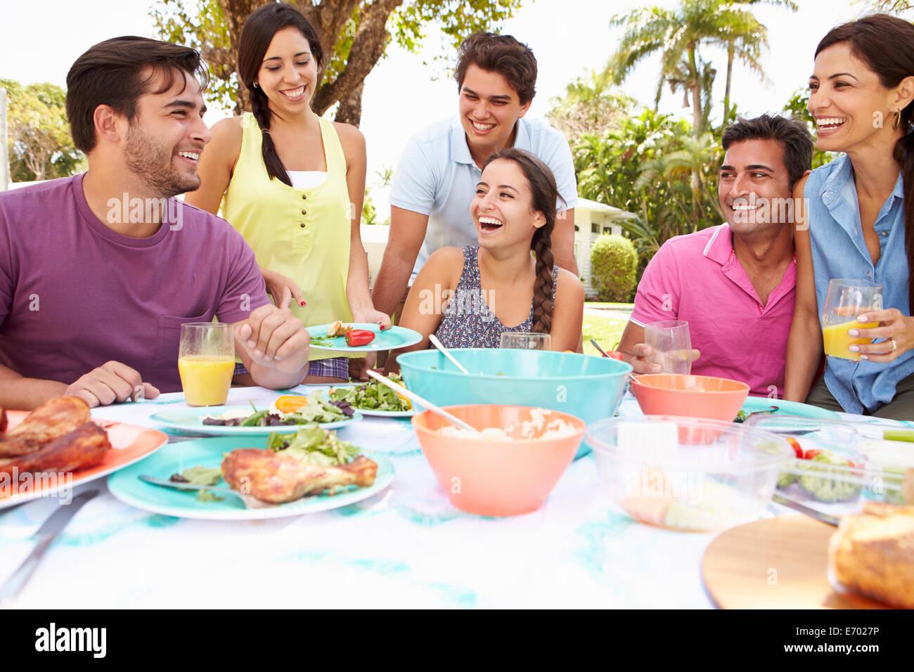 Gruppe von Freunden, feiern, Essen im Garten zu Hause genießen Stockbild