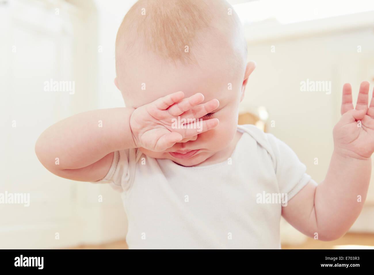 Nahaufnahme von müde Baby Boy mit Hand Augen bedecken Stockbild