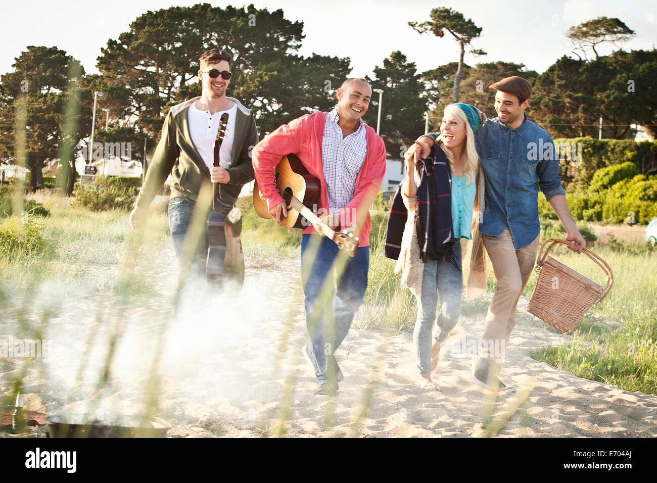 Vier Erwachsene Freunde mit akustischer Gitarre und Picknick-Korb am Strand von Bournemouth, Dorset, Großbritannien Stockbild