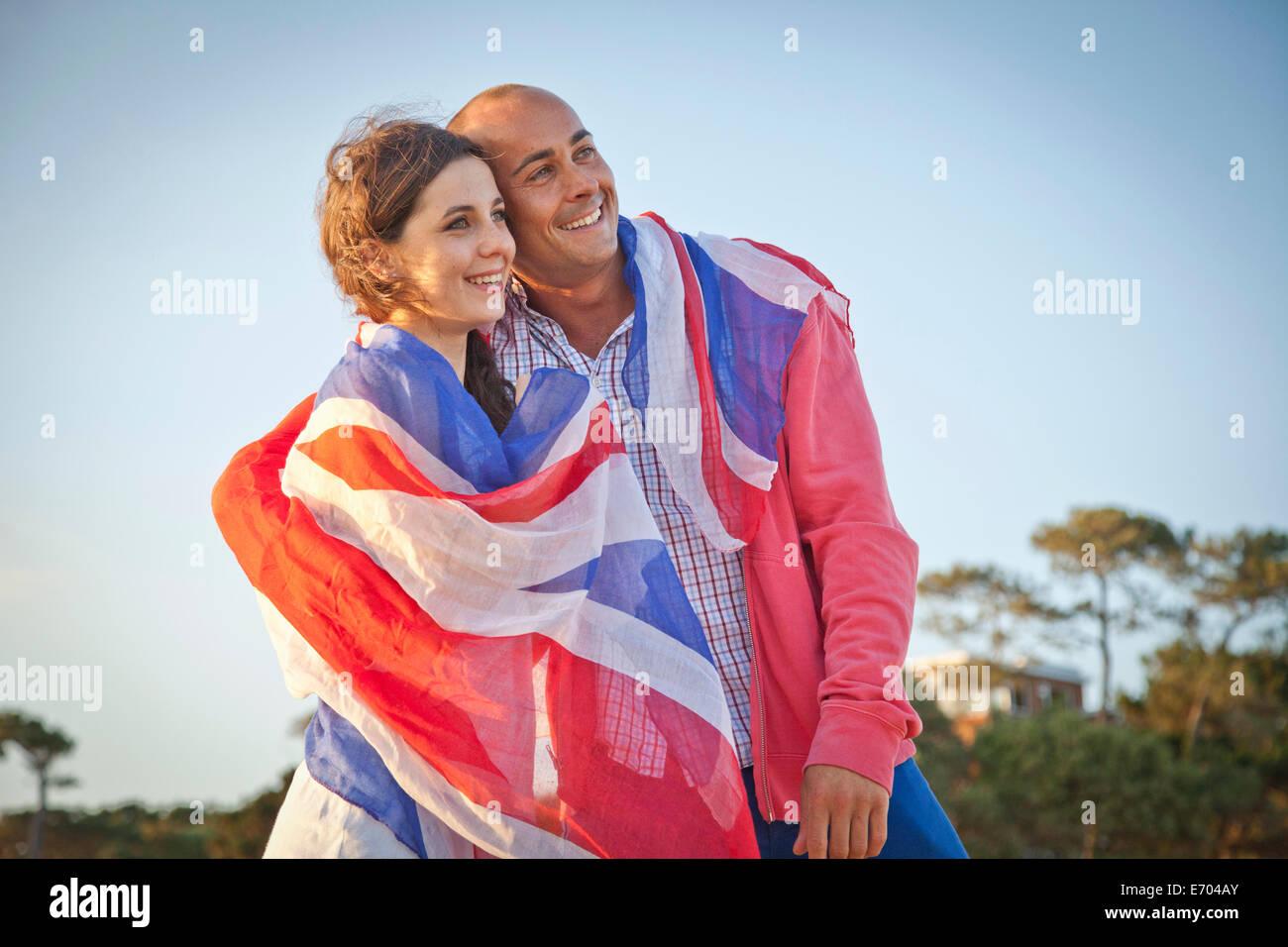 Paar verpackt in britische Flagge am Strand von Bournemouth, Dorset, Großbritannien Stockbild