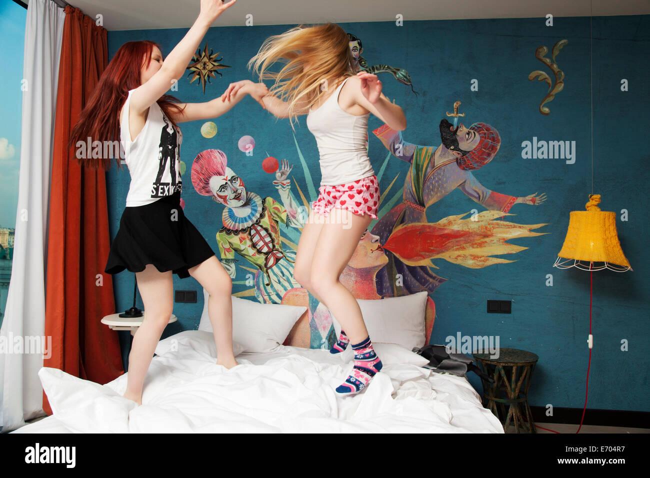 Zwei junge Frauen tanzen auf Hotelbett Stockbild