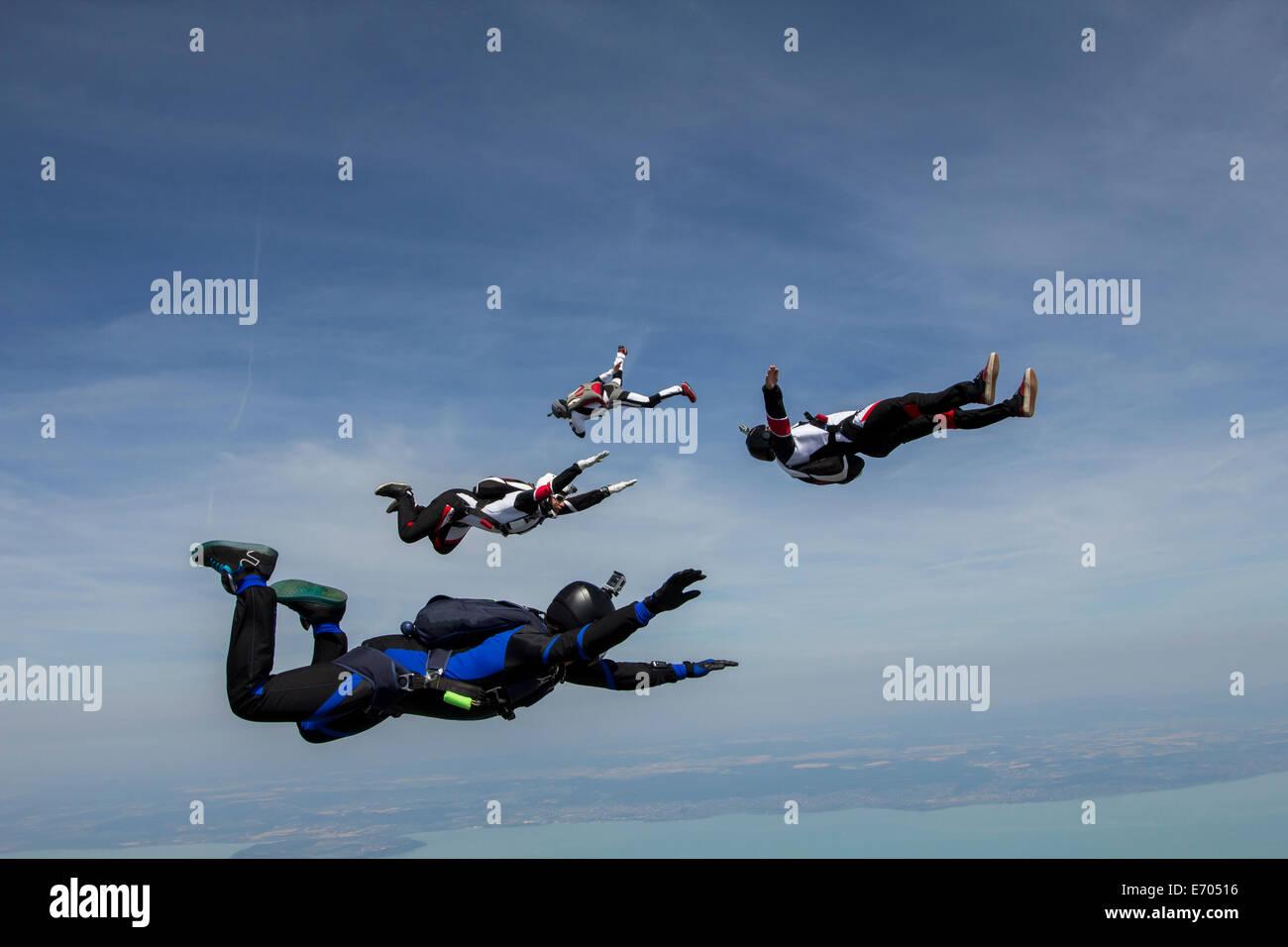 Vier junge Erwachsene männliche Fallschirmspringer frei fallend, Siofok, Somogy, Ungarn Stockbild