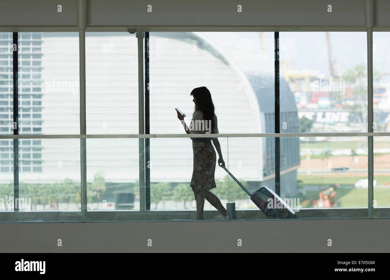 Junge Frau mit Smartphone und ziehen Koffer im Flughafen Stockbild