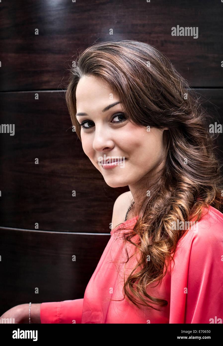 Porträt der jungen Frau im Friseursalon mit langen Ringletted brünette Haare Stockbild