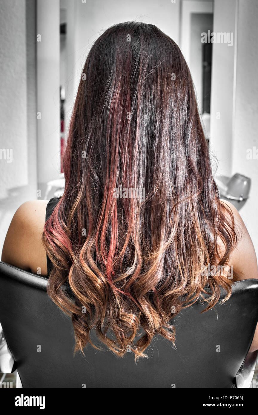 Rückansicht des jungen Frau im Friseursalon mit lange brünette Haare mit Wellen und rosa highlights Stockbild