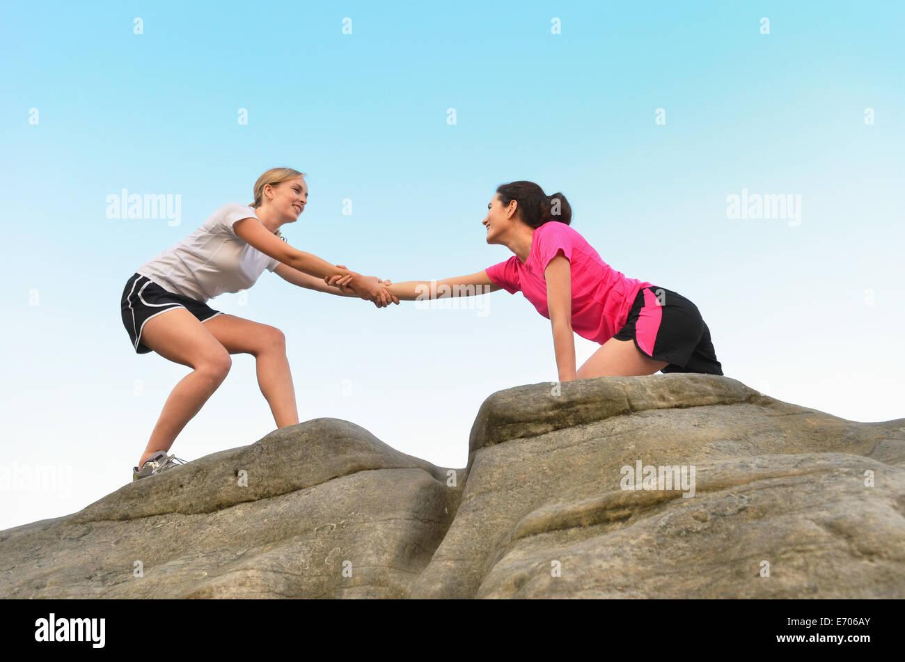 Junge weibliche Läufer Freund zum Seitenanfang Felsformation helfen Stockbild