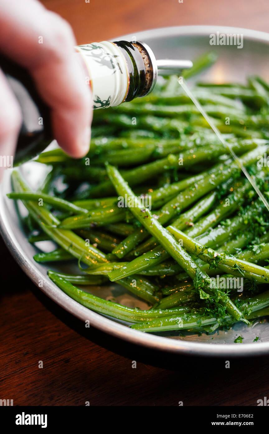 Person gießen Sauce auf grünen Bohnen Stockbild