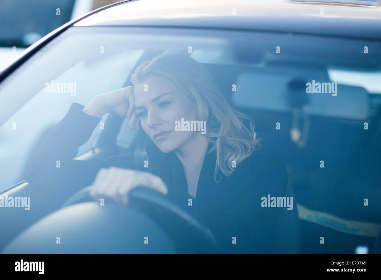 Gelangweilte Geschäftsfrau starrte während der Fahrt in die Stadt-Stau Stockbild