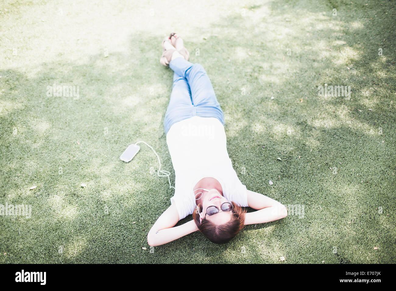 Draufsicht Mitte erwachsenen Frau liegend und anhören von Kopfhörer im park Stockbild