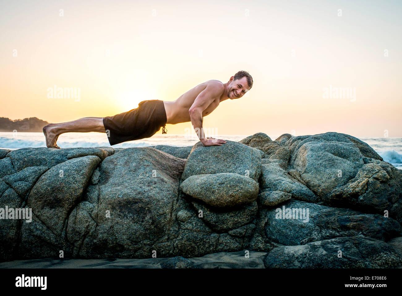 Mitte erwachsenen Mannes macht Liegestütze auf Felsen am Strand Stockbild