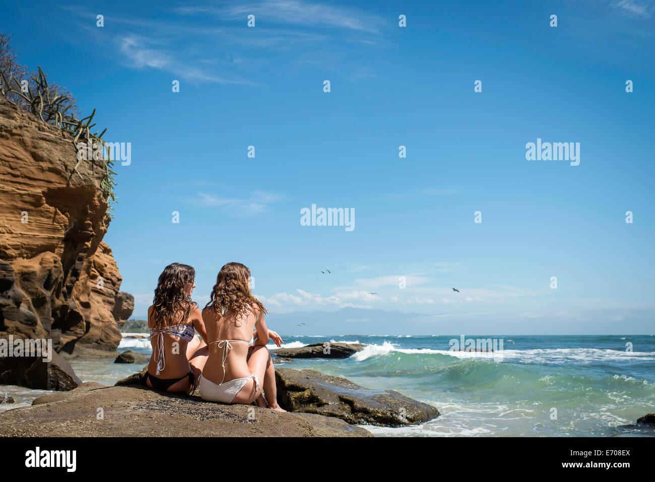 Zwei junge Frauen sitzen auf Felsen, Blick auf das Meer Stockbild
