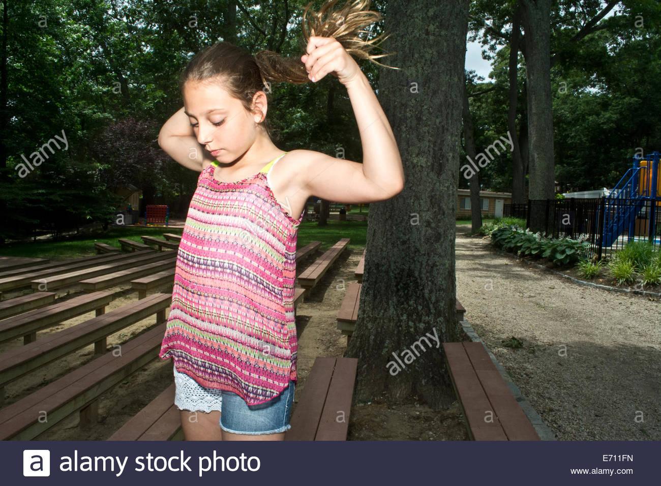 Binden ihr langes Haar zu Pferdeschwanz am Sommerlager Mädchen Stockbild