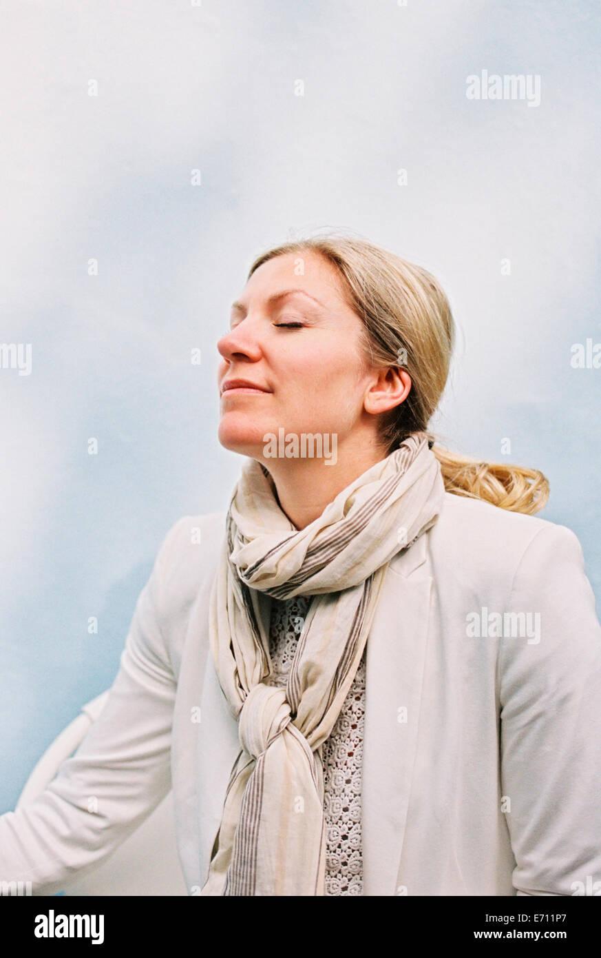 Eine Frau mit blonden Haaren sitzen mit geschlossenen Augen und ihr Kopf schräg zurück, das Gefühl Stockbild