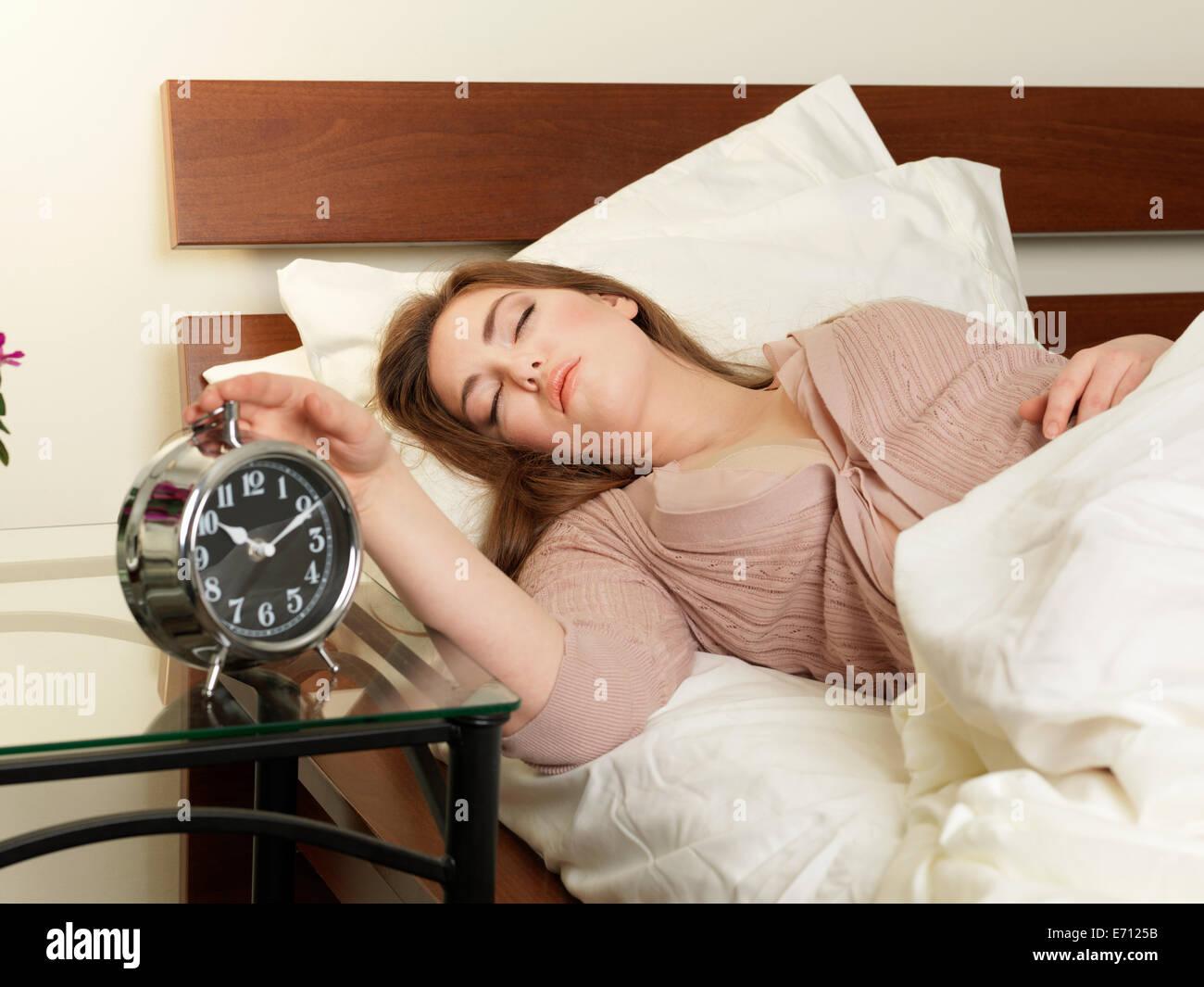 Verträumte junge Frau Wecker aus dem Bett ausschalten Stockbild