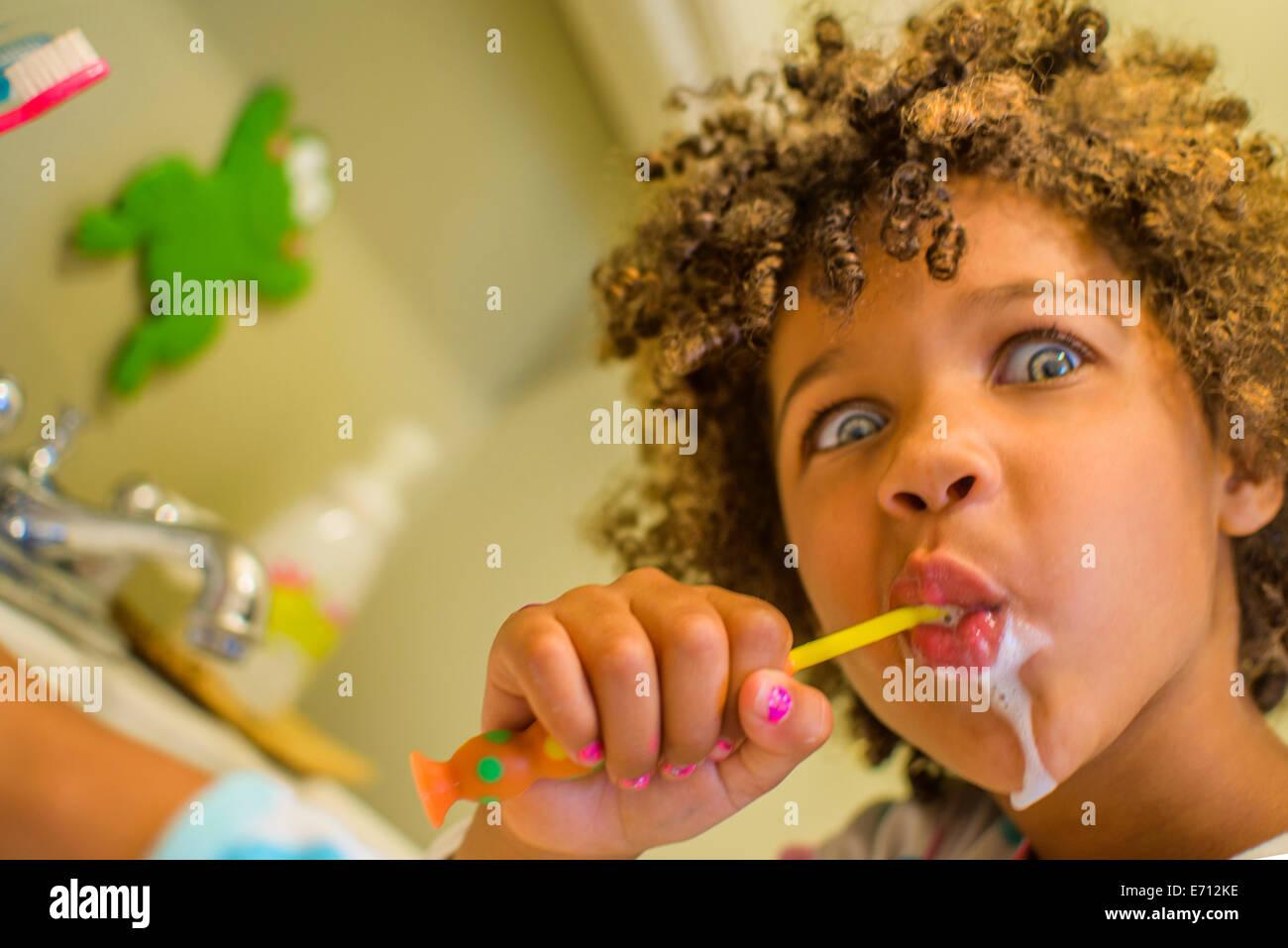 Porträt eines Mädchens Gesicht ziehen, während Zähneputzen Stockfoto