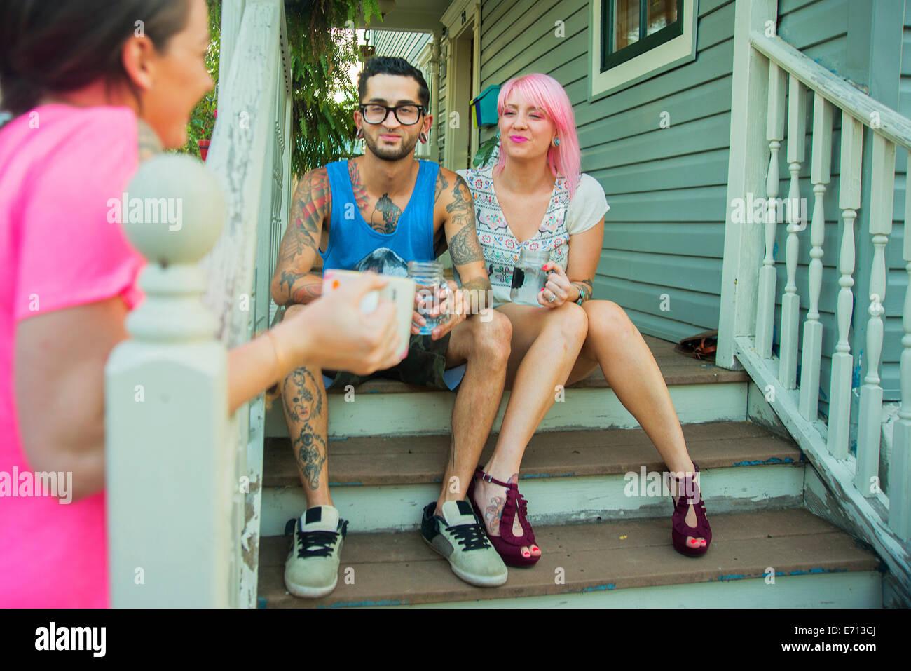 Junge Erwachsene Freunde im Chat vor der Veranda Schritte Stockbild