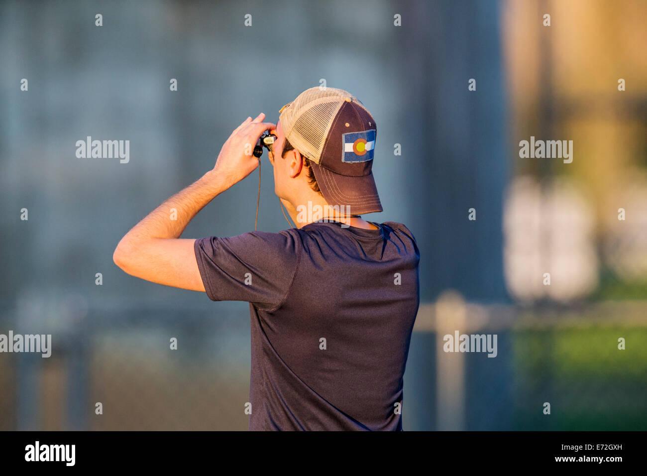 Junger mann mit dem fernglas vogelbeobachtung fischadler stockfoto