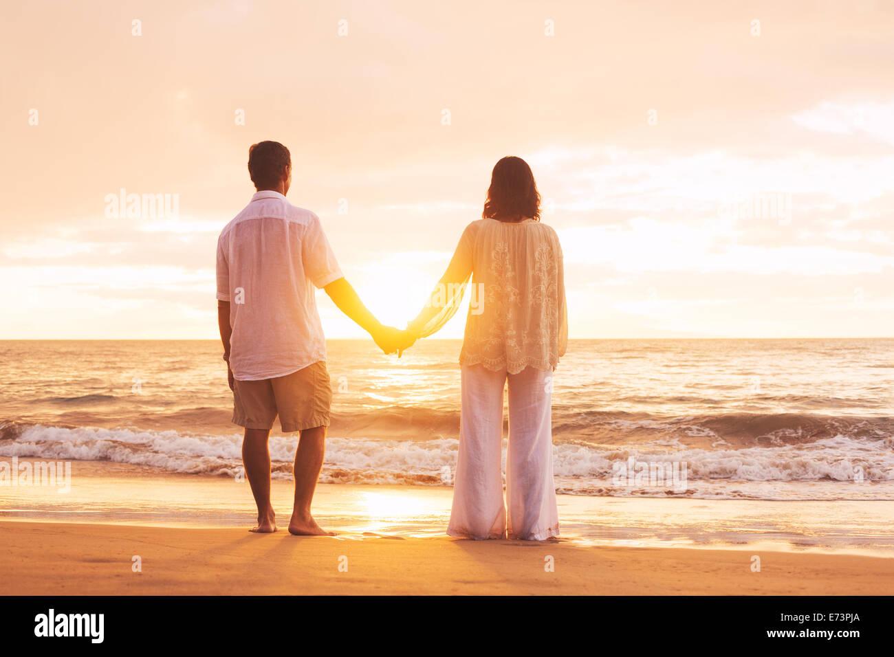 Romantische älteres paar Sonnenuntergang am Strand genießen Stockbild