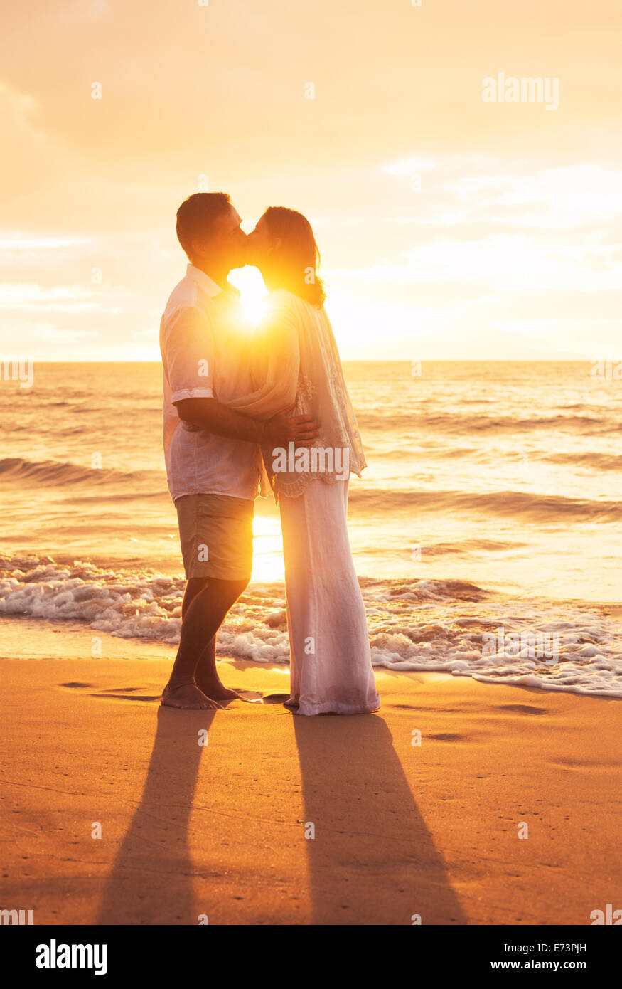 Romantische älteres Paar küssen bei Sonnenuntergang am Strand Stockbild