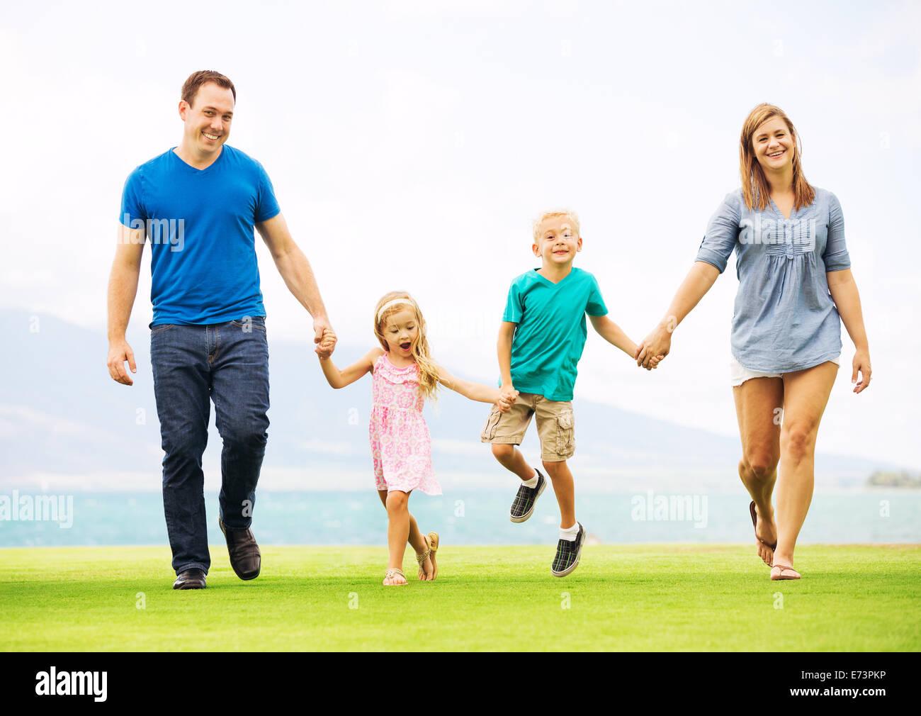 Glückliche Familie draußen auf dem Rasen Stockbild