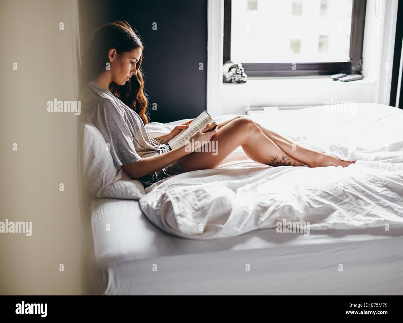 Seitenansicht der junge Frau sitzt auf ihrem Bett und las ein Buch zu Hause im Schlafzimmer Stockbild