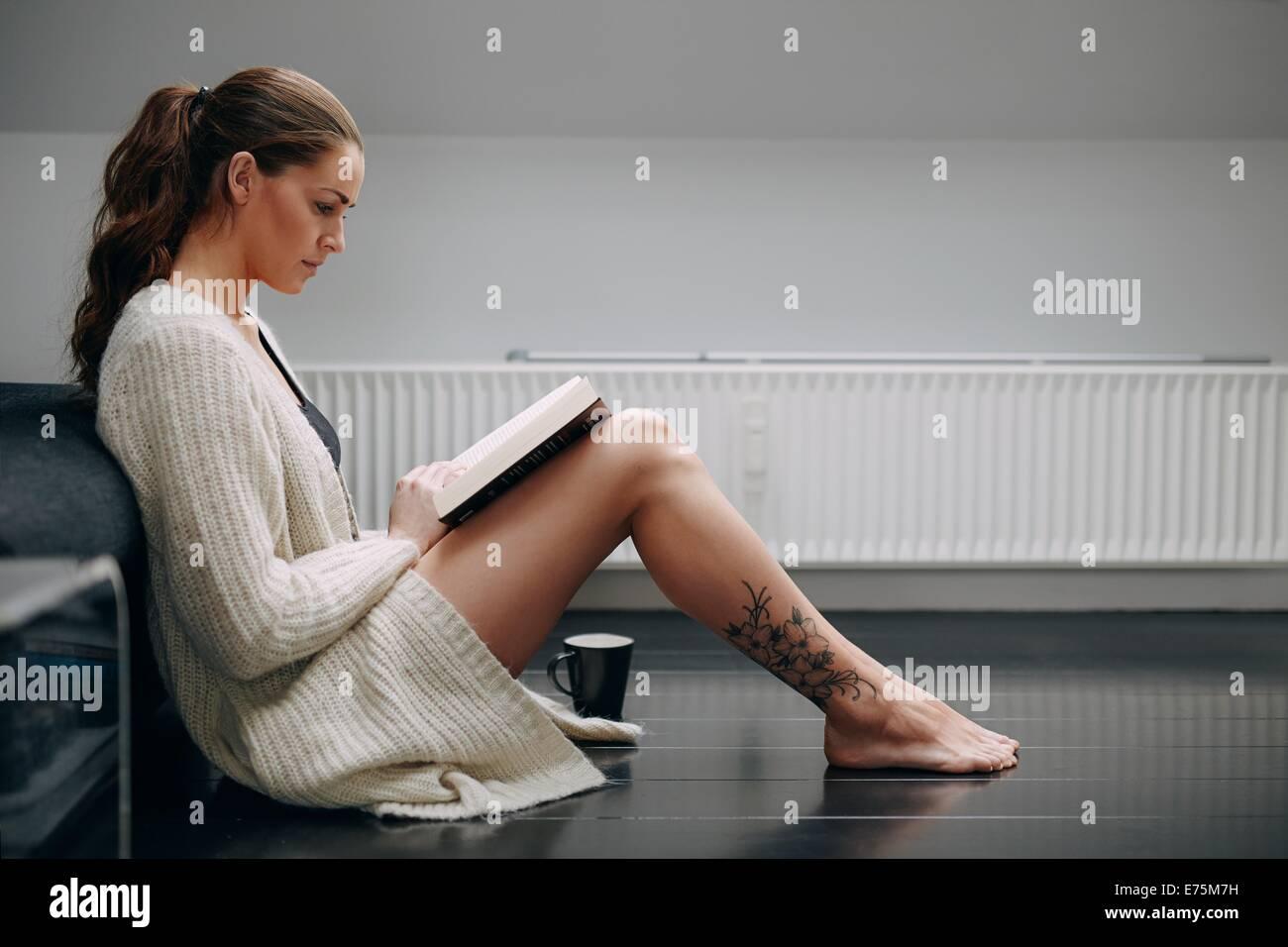 Seitlicher Blick auf schöne junge Dame ein Buch zu lesen. Kaukasisches weibliches Modell zu Hause sitzen am Stockbild