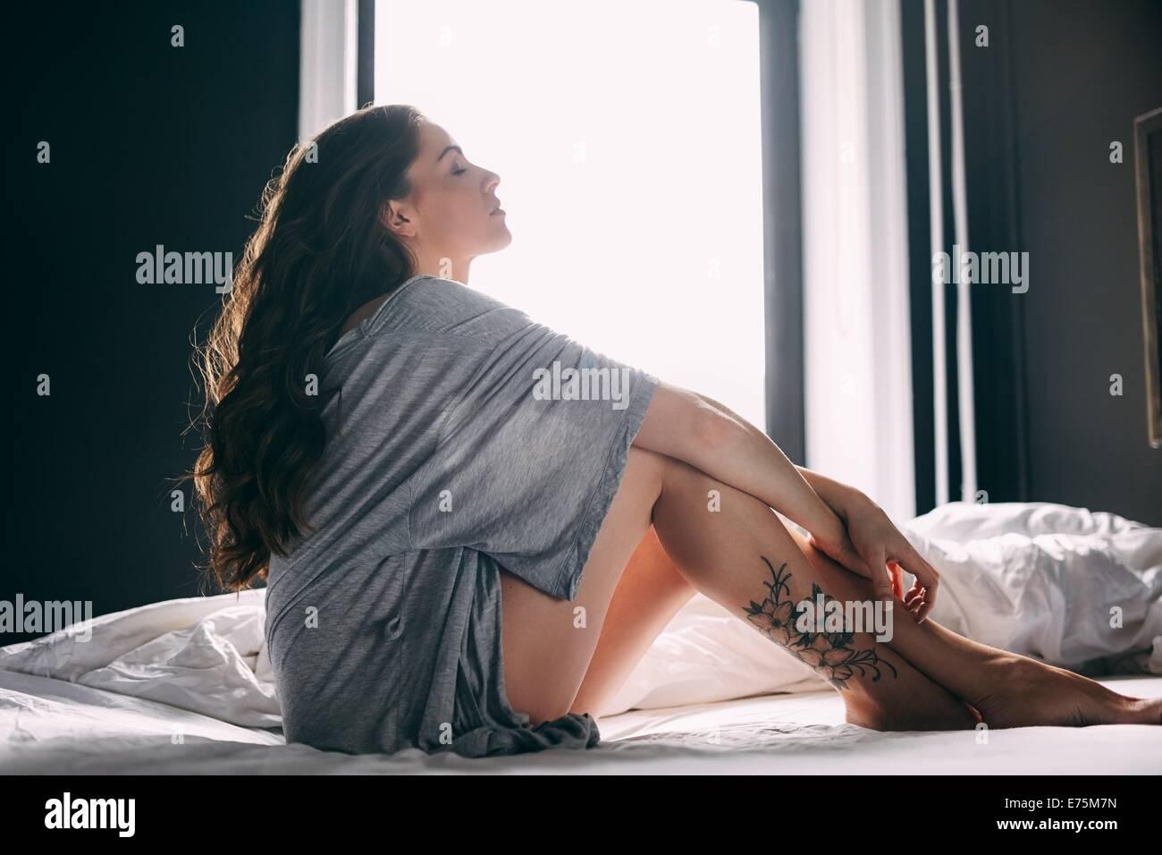 Seitenansicht der Frau sitzt entspannt auf Bett mit geschlossenen Augen. Entspannte Frau im Schlafzimmer. Stockbild