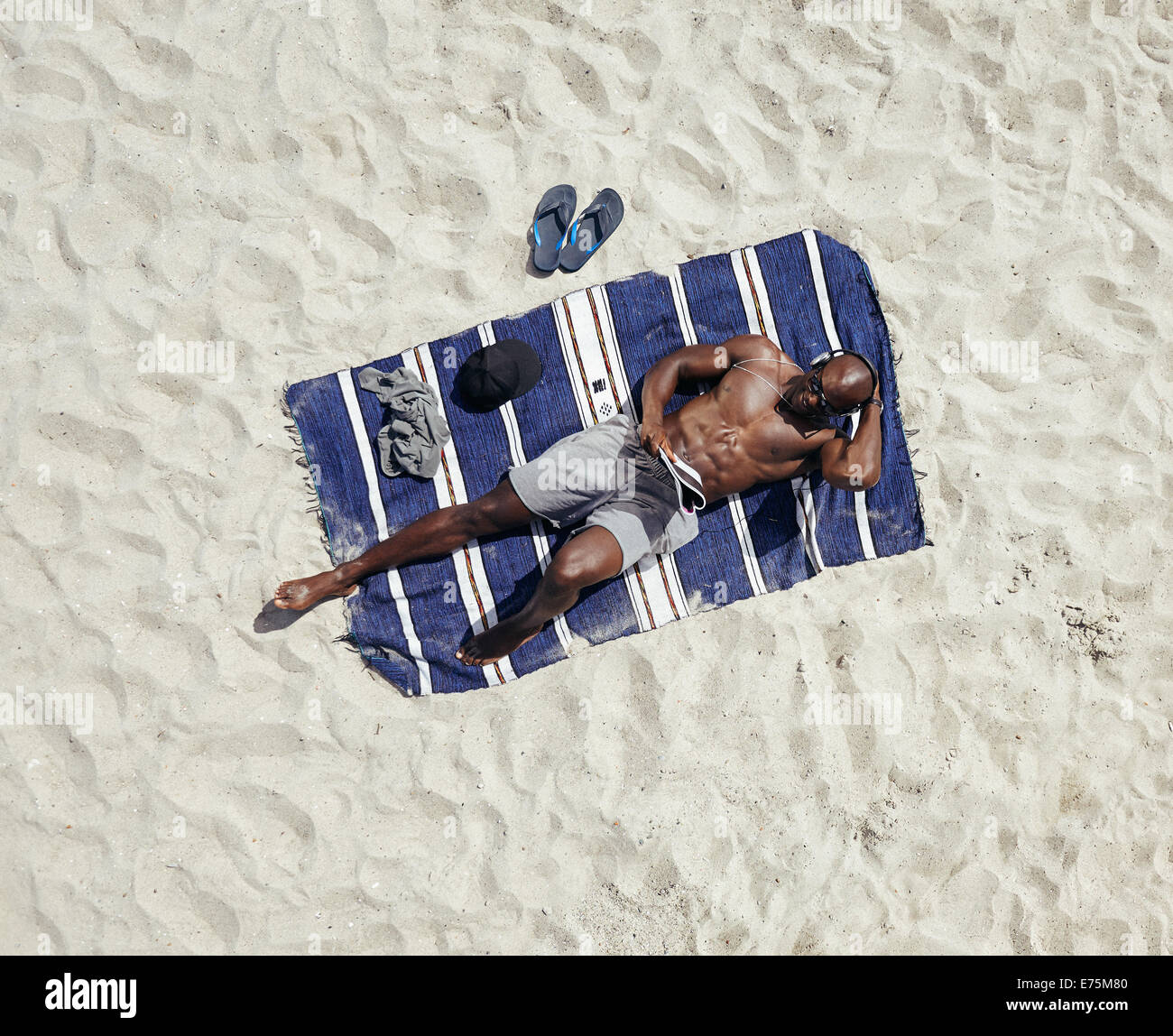 Draufsicht der junge Kerl nacktem Oberkörper liegend auf einer Matte, die eine Zeitschrift liest. Afrikanische Stockbild