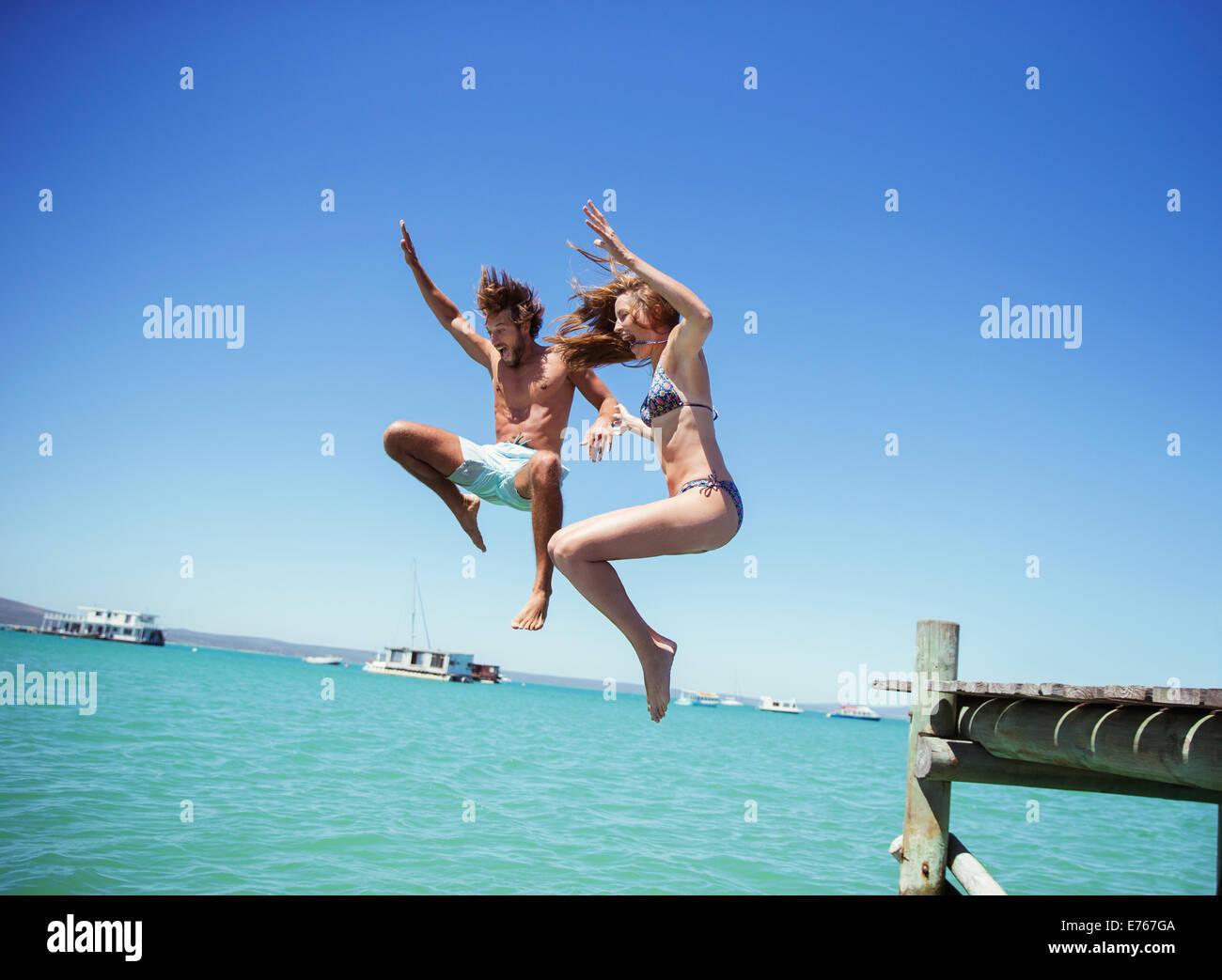 Paar springen aus hölzernen Dock zusammen Stockfoto