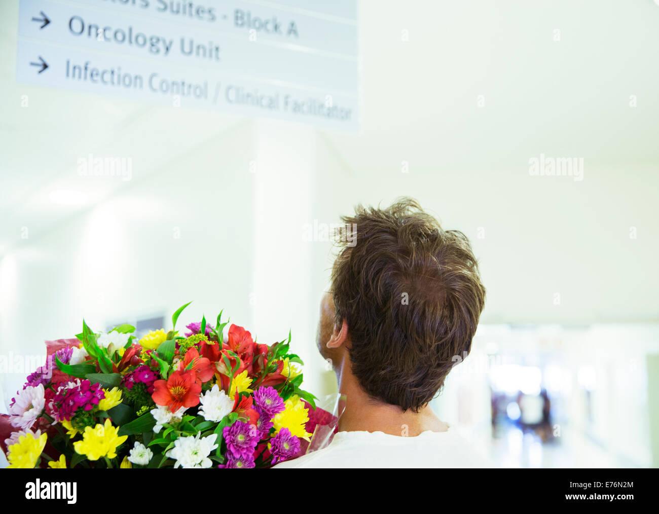 Mann mit Blumenstrauß im Krankenhaus Stockbild