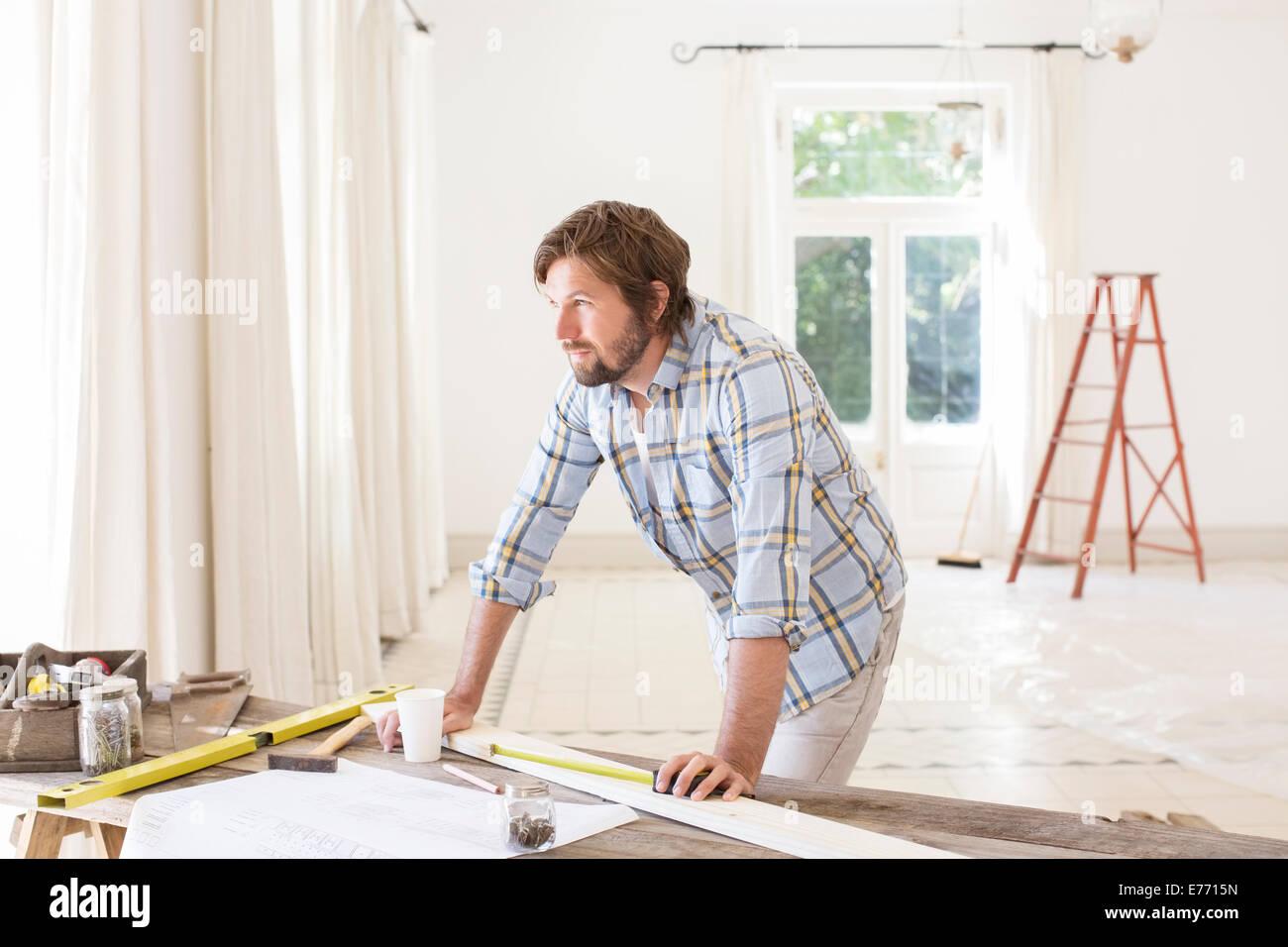 Mann mit Blick auf Bau Tisch im Wohnraum Stockbild