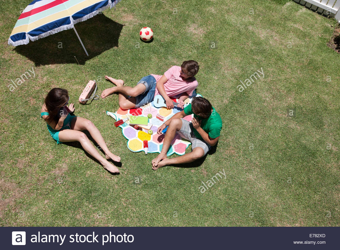 Freunde, Sonnenbaden und Relaxen auf dem sonnigen Rasen Stockbild