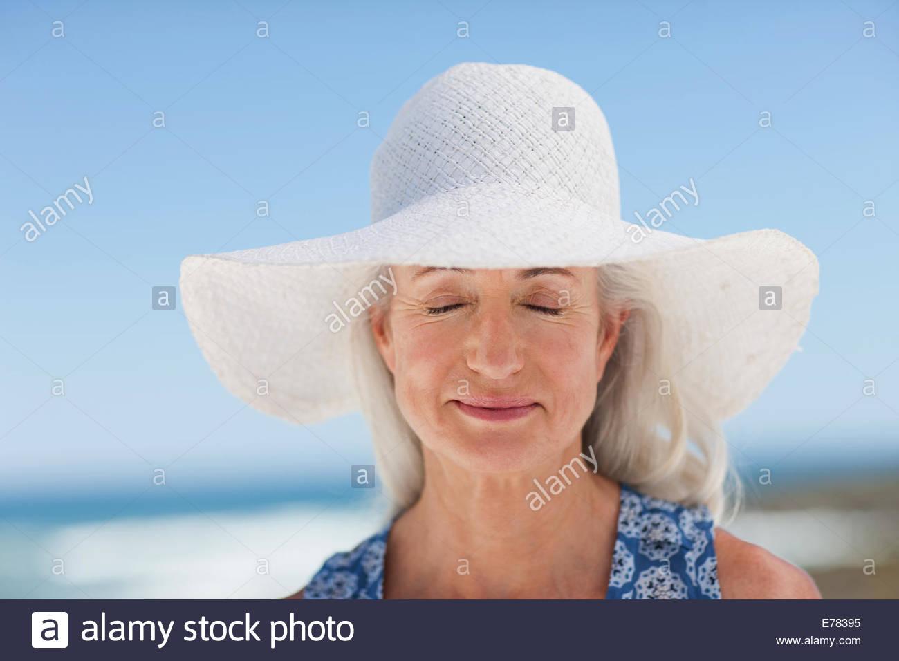 Nahaufnahme von Frau schließen der Augen mit dem Sonnenhut tragen Stockbild