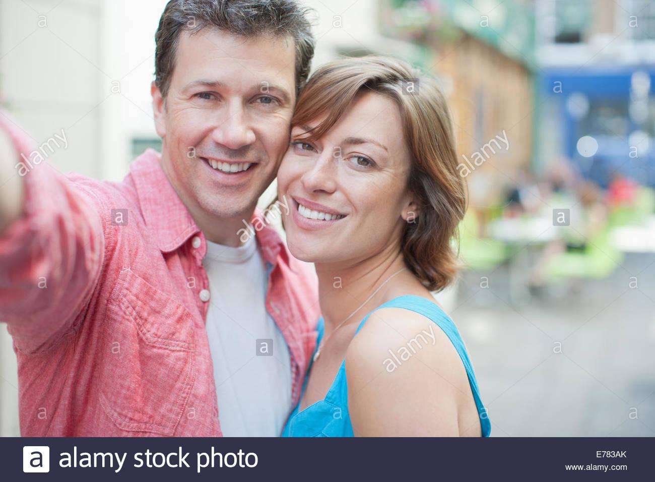 Verspieltes paar lächelnd im freien Stockbild