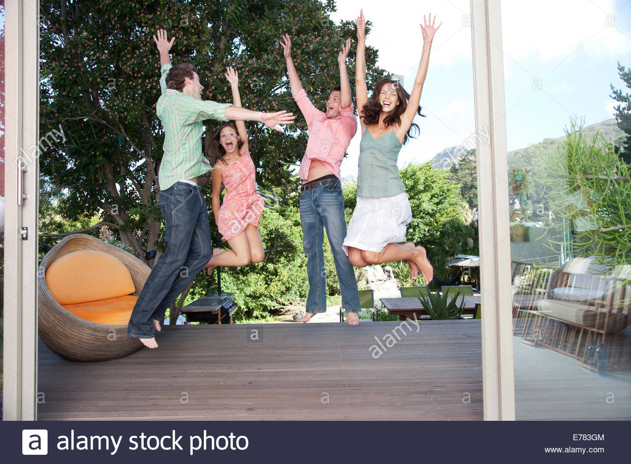 Freunde auf einem Deck herumspringen Stockbild