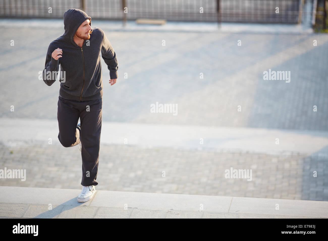 Porträt des jungen mannes in activewear joggen draußen stockfoto