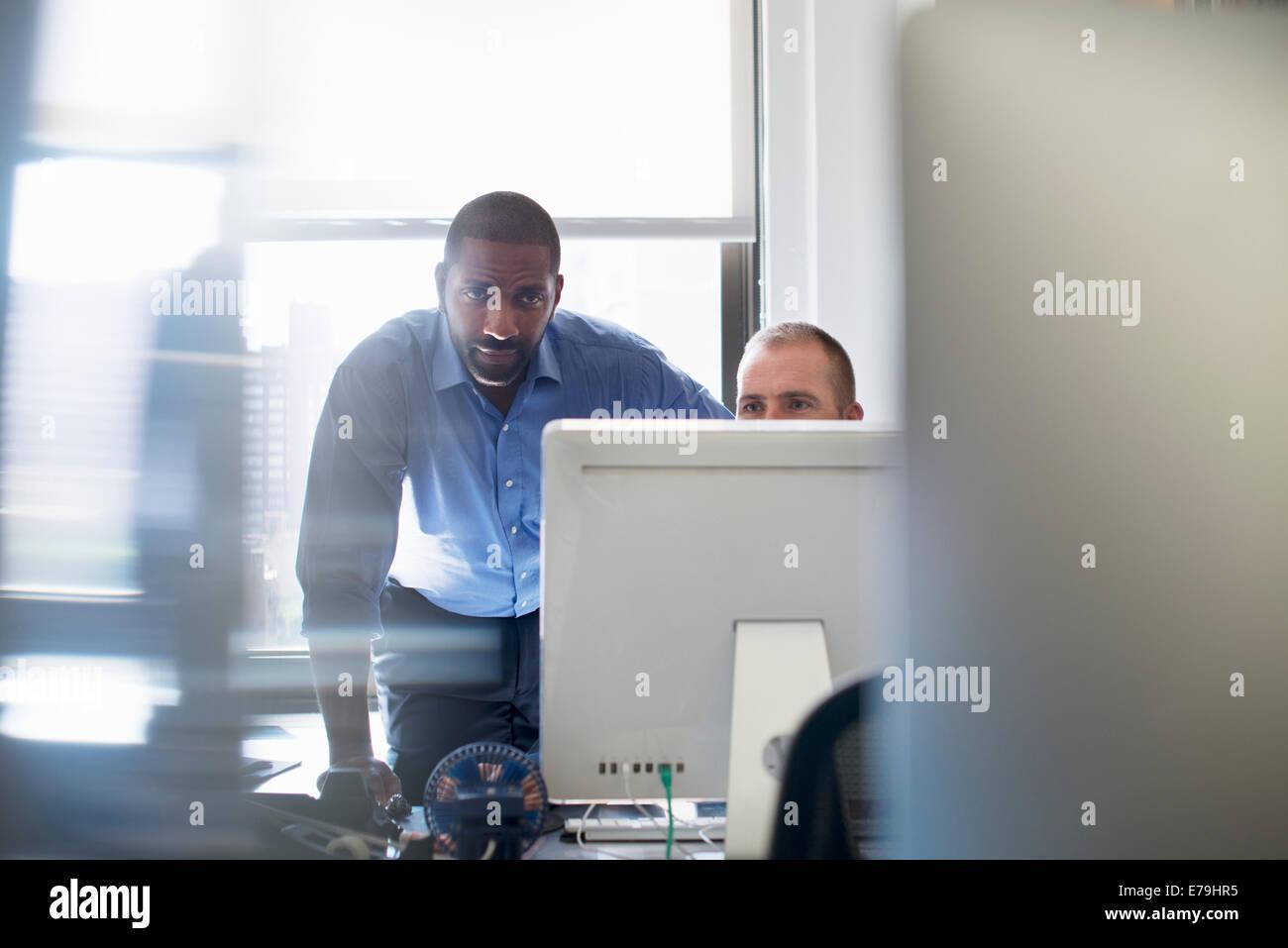 Zwei Männer in einem Büro arbeiten, beide mit Blick auf einem Computer-Monitor. Stockbild