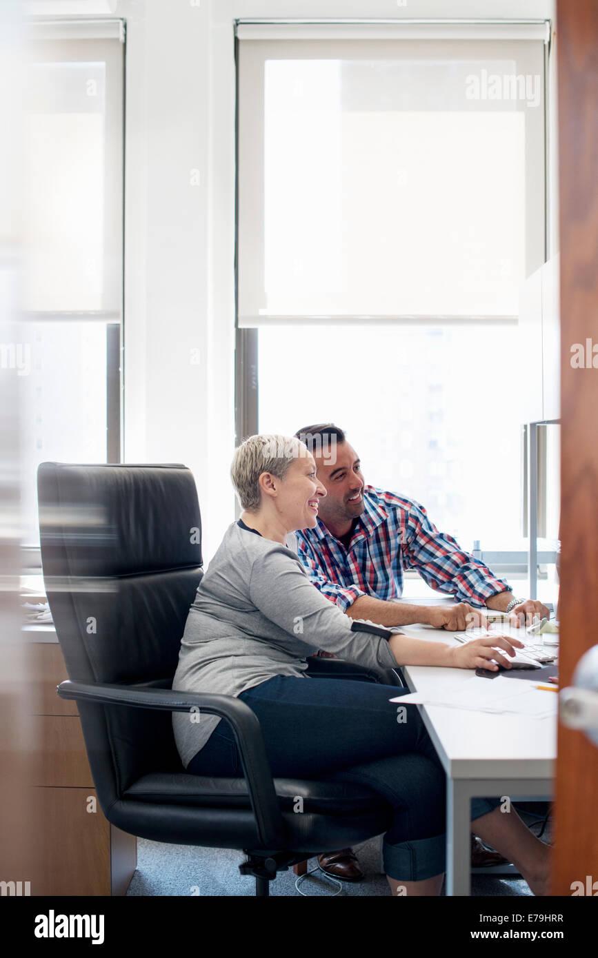 Zwei Menschen, Kolleginnen und Kollegen in einem Büro, einem Computer-Bildschirm betrachten. Stockbild