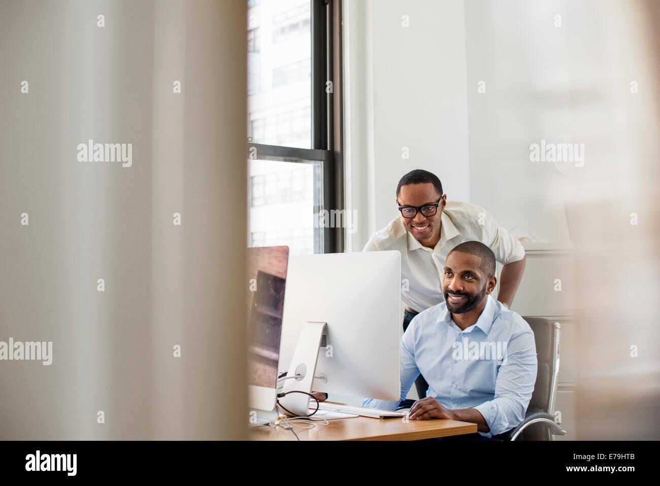 Zwei Männer auf der Suche auf einem Computer-Bildschirm in einem Büro. Stockbild