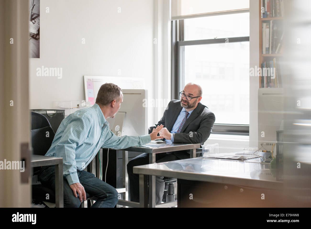 Büroalltag. Zwei Männer sitzen, miteinander zu reden. Stockbild