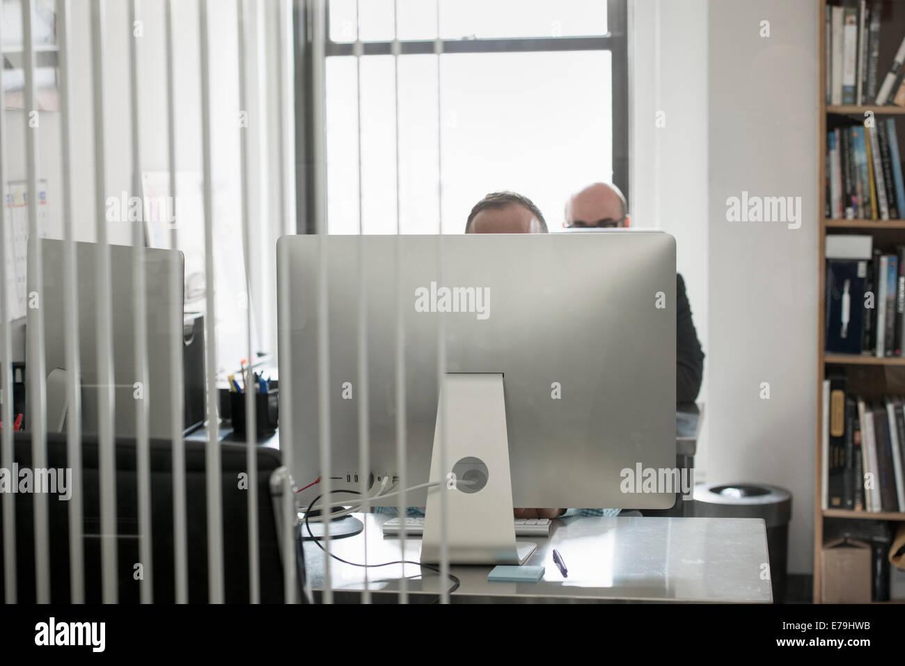 Büroalltag. Zwei Menschen sitzen an einem Schreibtisch hinter einem Computer-terminal. Stockbild