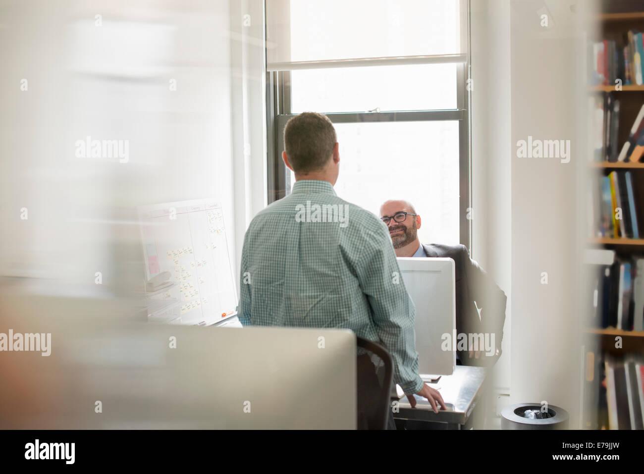 Büroalltag. Zwei Menschen, Geschäftsleute, die über ihre Schreibtische miteinander zu reden. Stockbild
