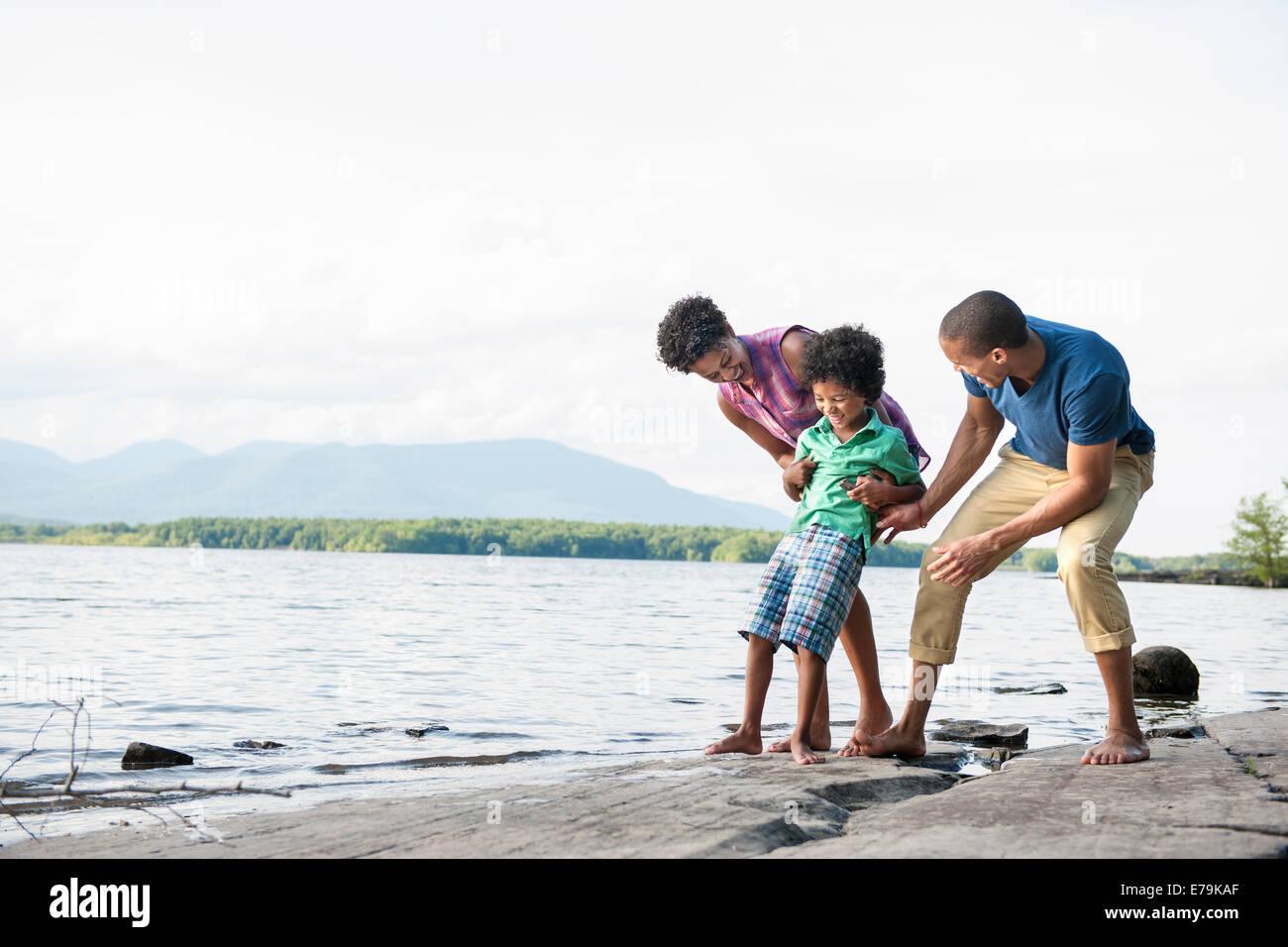 Familie, Mutter, Vater und Sohn spielen am Ufer eines Sees. Stockbild