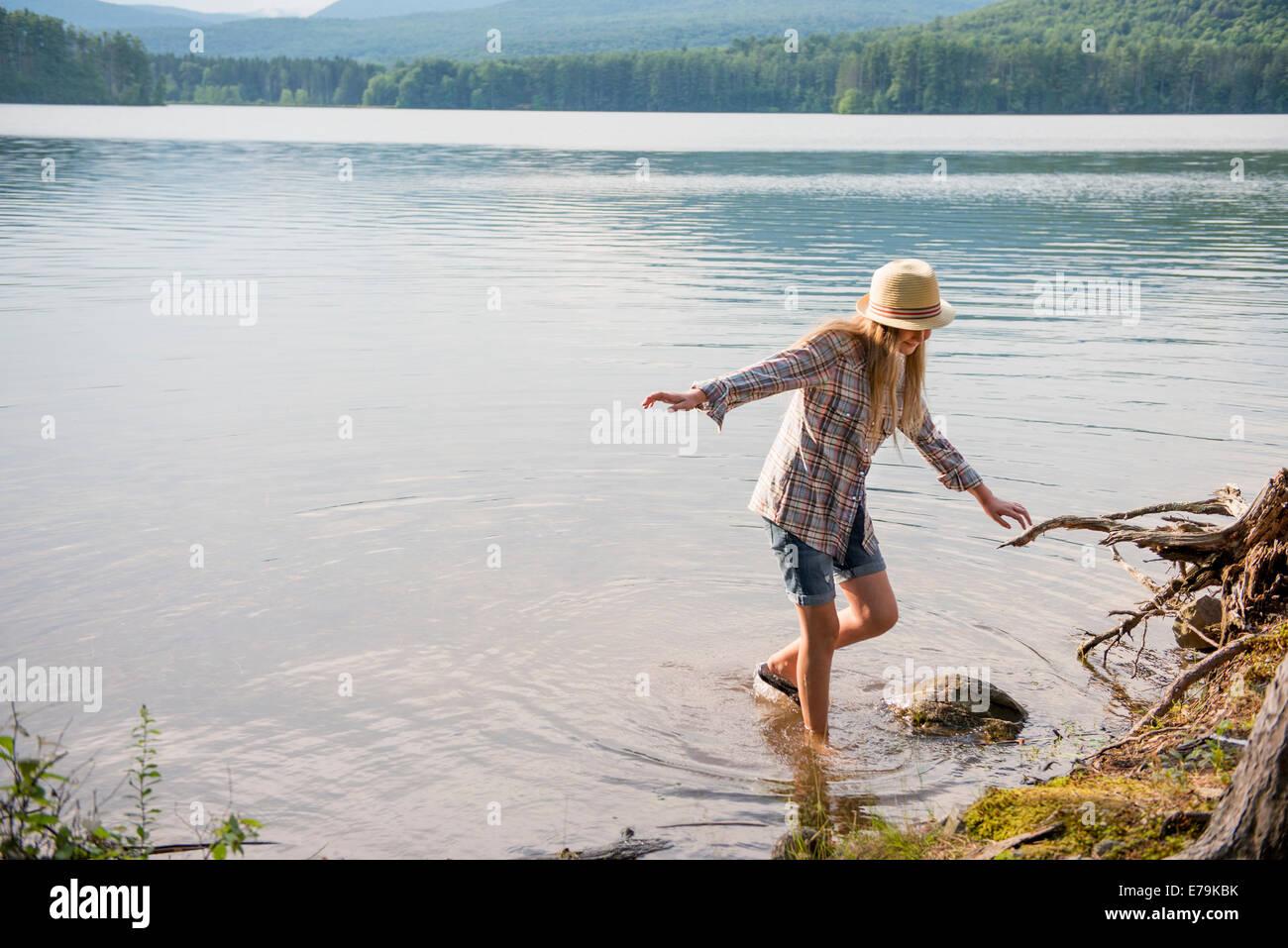 Ein junges Mädchen in einem Strohhut und Shorts Paddeln im flachen Wasser eines Sees. Stockfoto