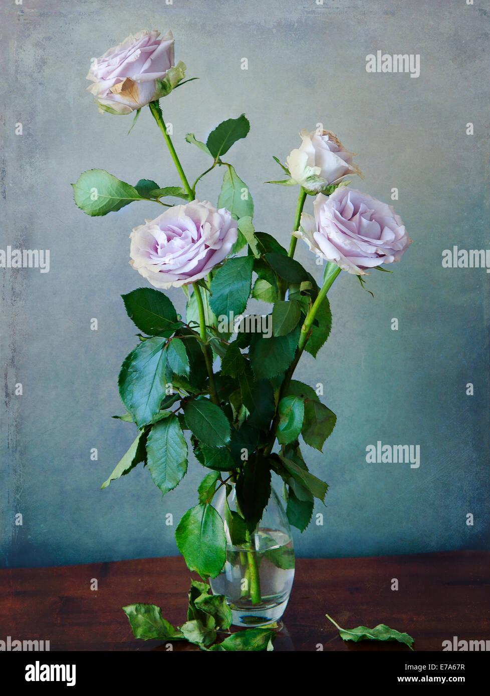 Vintage Still Innenlebens: romantische rosa Rosen im Glas auf einem hölzernen Tisch und Grunge Textur Stockfoto