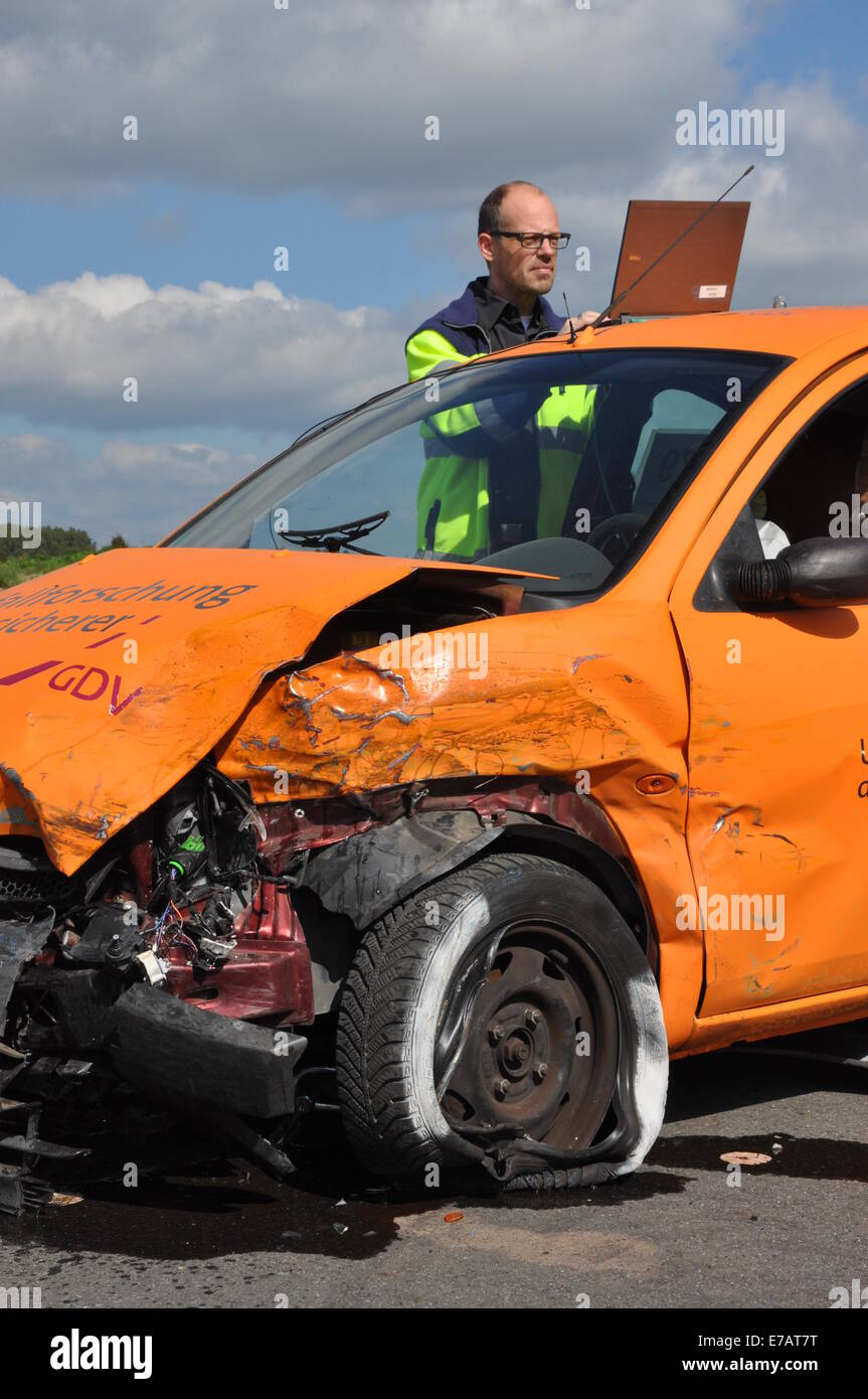 Ein Bediensteter dokumentiert die Schäden auf einer orange Auto ...